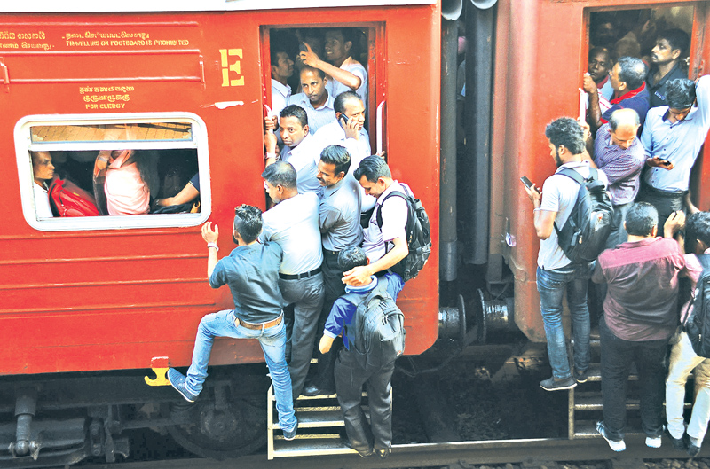 Train travellers clinging on to foot boards bound home in the available trains that plied during the strike for the past six days. Picture by Saman Mendis.