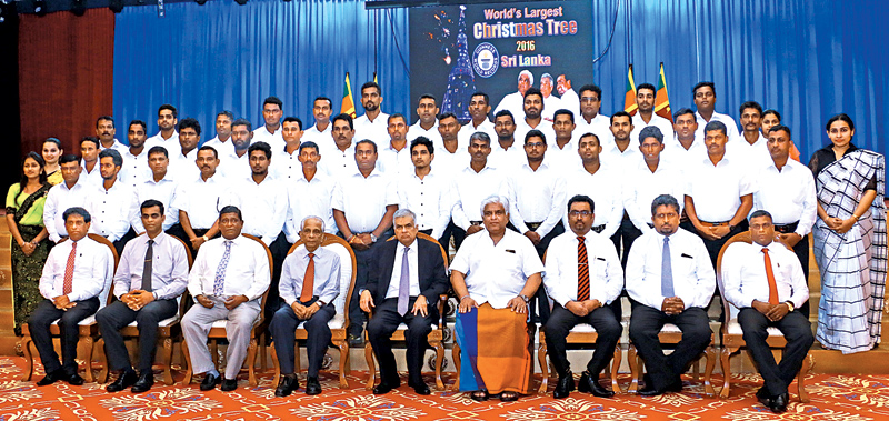 Prime Minister Ranil Wickremesinghe and Minister Arjuna Ranatunge with the team which constructed the world's tallest artificial Christmas tree at Galle Face grounds last year. A ceremony was held at Temple Trees yesterday, where Minister Ranatunge handed over the Guinness records certificate which declared the Christmas tree at Galle Face grounds as the world's tallest artificial Christmas tree, to Prime Minister Wickremesinghe. Picture by Hirantha Gunatileke
