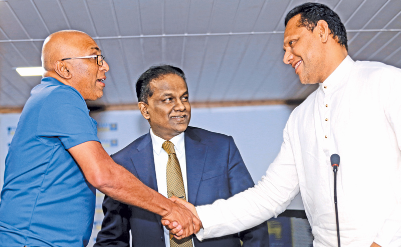 Sports Minister Dayasiri Jayasekera congratulates Chandika Hathurusingha who took over officially as Sri Lanka cricket's head coach at the press conference held at SLC headquarters yesterday. SLC president Thilanga Sumathipala is also present. Pic by Rukmal Gamage