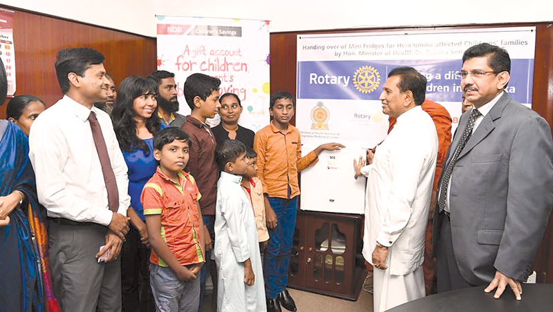 Health Minister Dr. Rajitha Senaratne chatting with the children after handing over the refrigerators, while Health Services Director General Dr. Anil Jasinghe looks on.