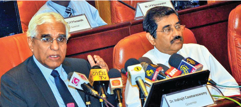 Central Bank Governor Dr Indrajit Coomaraswamy speaks at the media conference to announce the eighth monetary policy review. Senior Deputy Governor Nandalal Weerasinghe looks on. Picture by Thushara Fernando