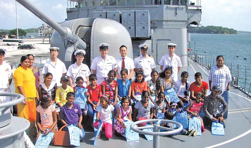 The SETOGIRI (DD-156) crew with local children on board the ship.