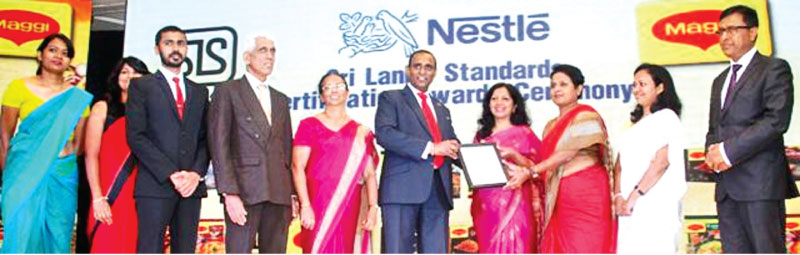 Sri Lanka Standards Institution Chairman Pradeep Gunawardana, presenting the SLS Certificate to Priyadarshinie Karunaratne, Vice President – Food and  to Shivani Hegde, Managing Director at Nestle flanked by Nestle and Sri Lanka Standards Institution officials. Picture by Chaminda Niroshana