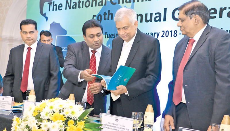 President of the National Chamber of Commerce Sujeewa Samaraweera presenting the Chamber's 59th annual report to Prime Minister Ranil Wickremesinghe at an event held at the Kingsbury Hotel yesterday. Picture by Hirantha Gunathilaka