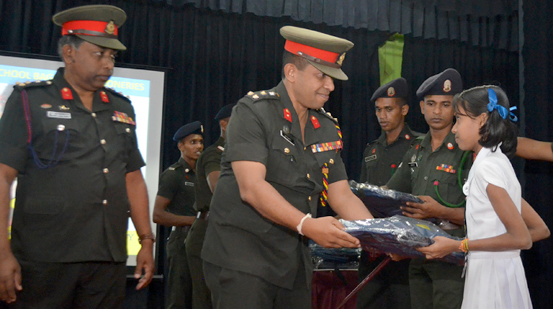 An Army officer presenting a student with a schoolbag, while Security Forces Commander Major General Darshana Hettiarachchi looks on.