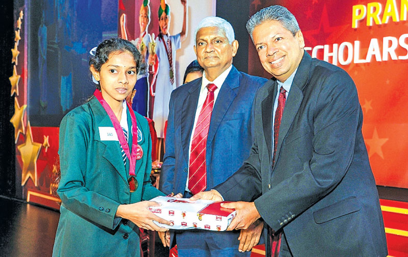 A Pranama recipient receives a National Merit Award from Chief Guest Professor Ajantha Dharmasiri  and Ceylinco Life Managing Director R. Renganathan.