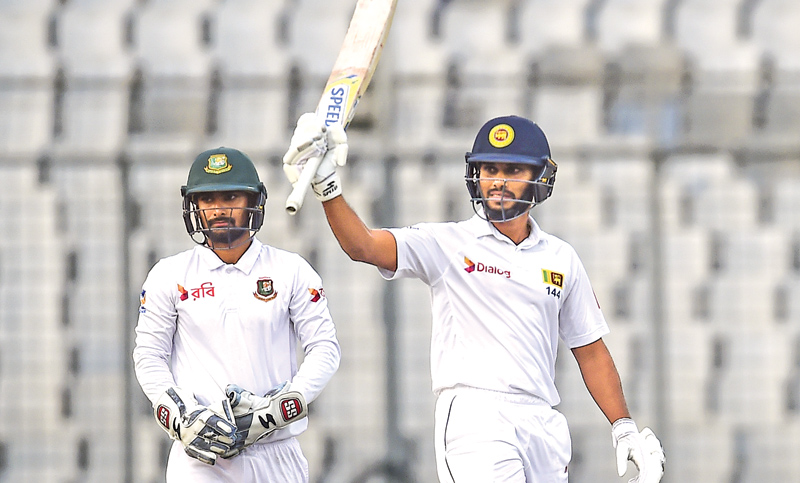 Sri Lankan cricketer Roshen Silva (R) reacts after scoring a half century (50 runs) as Bangladeshi wicketkeeper Liton Das (L) looks on. AFP