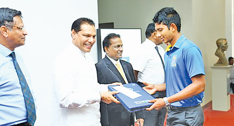 A player receiving an annual domestic contract from Sports Minister Dayasiri Jayasekera at the Ministry of Sports Duncan White Auditorium yesterday. SLC president Thilanga Sumathipala is also present.