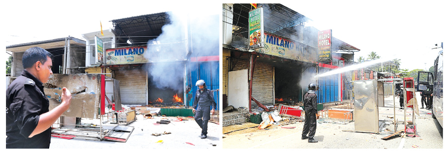 Police officials are seen dousing the fire in shops in Ambatenna town in the Kandy district after mobs went on the rampage yesterday. The situation has been brought under control by the security forces and the police. Pictures by Rukmal Gamage