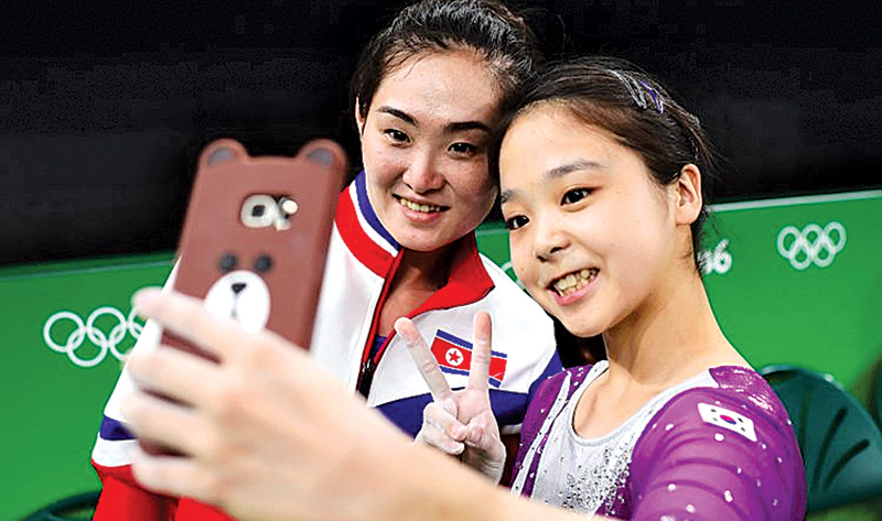 Olympic gymnasts Lee Eun-Ju, 17, from South Korea and Hong Un Jong, 27, from North Korea, pose for a photo together during the recently concluded PyeongChang 2018 Winter Olympic Games in South Korea.- AFP