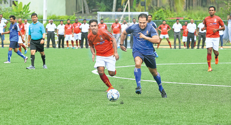 Sports Minister Dayasiri Jayasekara vying for the ball against an FFSL team player during the friendly match.