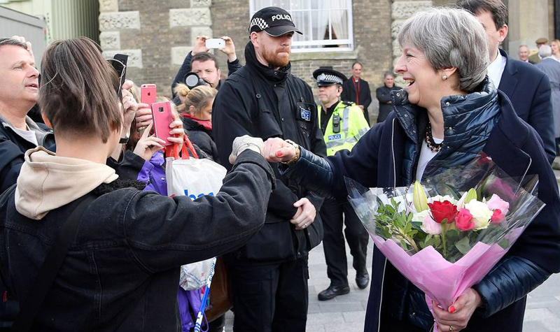 British Prime Minister Theresa May fistbumping a member of the public during her visit to Salisbury on Thursday where former Russian double agent Sergei Skripal and his daughter were found critically ill.