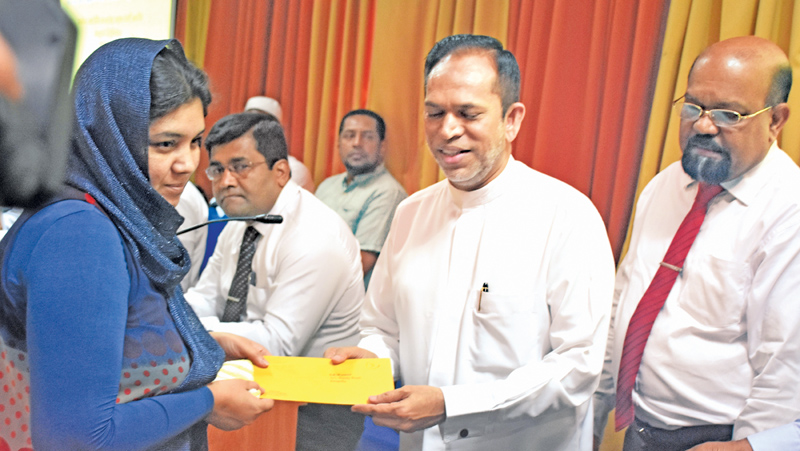 A beneficiary receiving compensation from State Minister M. L. M. Hisbullah . Post, Postal Services and Muslim Religious Affairs Minister A.M.H.A. Haleem was also present. Picture by Asela Kuruluwansa.