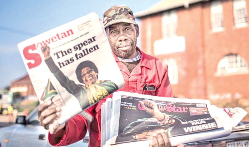 A newspaper seller holds up an edition featuring a story on the death of South African  anti-apartheid campaigner Winnie Madikizela-Mandela, in Johannesburg on Tuesday.- AFP