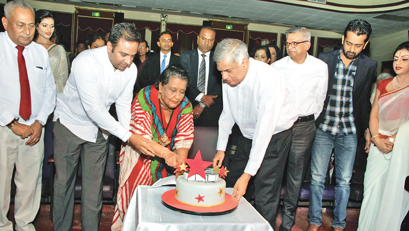 Prime Minister Ranil Wickremesinghe cutting the birthday cake with Sumitra Peries