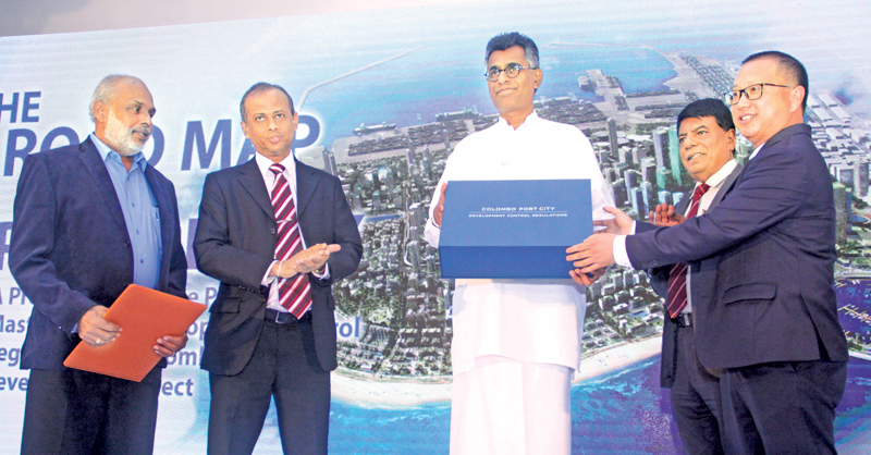 Megapolis and Western Development Minister Patali Champika Ranawaka being presented with the Proposed Masterplan and Development Control Regulations (DCR) of the Colombo Port City Development Project by the CHEC Port City Colombo Managing Director Houliang Jiang at the Balmoral-Saphire Ballroom, Kingsbury Hotel, Colombo yesterday. Megapolis and Western Development Ministry Secretary Nihal Rupasinghe, Colombo Port City Project Director Nihal Fernando (Far Left) Urban Development Authority Chairman Dr Jagath