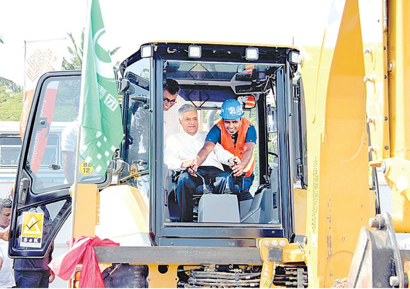 Prime Minister Ranil Wickremesinghe turning the first sod for the new middle-class housing complex in Sri Jayewardenapura Hospital Road in Thalapathpitiya yesterday. Megalopolis and Western Development Minister Patali Champika Ranawaka is  also in the picture. Picture by Hirantha Gunathilake.