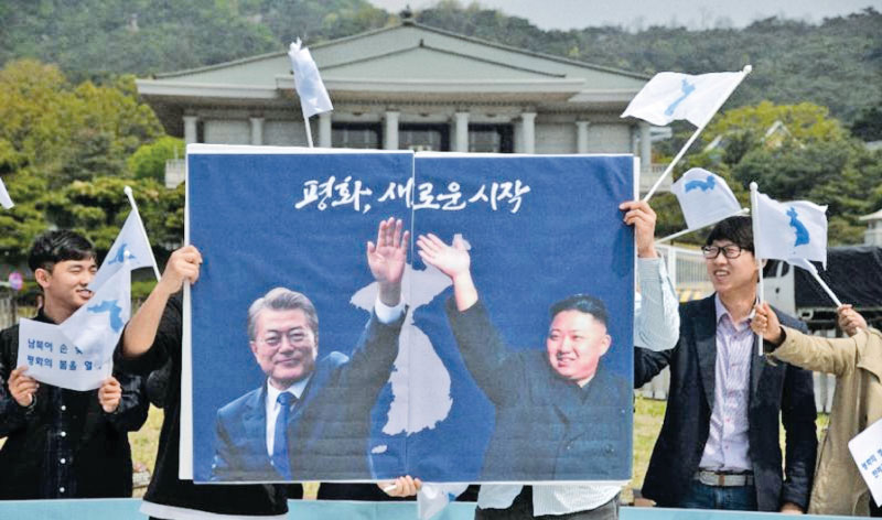 Activists hold a peace placard showing the leaders of North and South Korea at a rally IN Seoul. - AFP