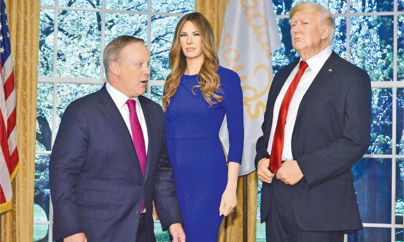 The waxwork of Melania Trump with her husband Donald at the Times Square Tussauds in New York. The real Sean Spicer looks on. - AFP