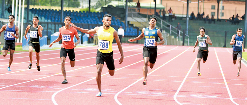 Vinoj Suranjaya (788) winning the men's 200 metres in a new Sri Lanka record of 20.68 seconds ahead of Himasha Eshan (242) who finished second and Dilip Ruwan (234) third at the Senior Athletic trials held at the Sugathadasa Stadium yesterday. Pix by Samantha Weerasiri