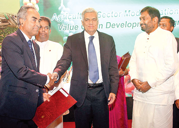 One of the local entrepreneurs who was qualified to receive the matching grant scheme of the Value Chain Development Programme at the agreement signing ceremony of the Agriculture Sector Modernization Project Value Chain Development Programme receiving the grant from Prime Minister Ranil Wickremesinghe at the Waters Edge in Battaramulla yesterday. Primary Industries Minister Daya Gamage was also present. Picture by Sulochana Gamage