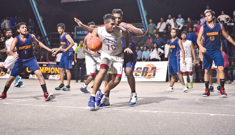 A CDB Finance player (white) is well guarded by a Moresand Ltd. attacker during the men's 'E' division final at Henry Pedris courts