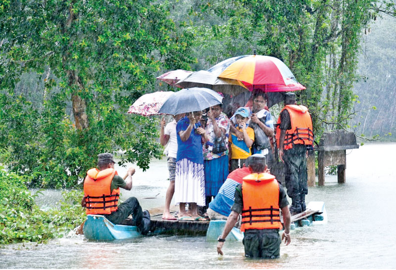 Incessant rains which the country has experienced since last Sunday triggered flash floods and landslides affecting thousands of people in the Southern, Sabaragamuwa, Western and Central Provinces. People being taken to safety in the Molkawa area in Bulathsinhala on a makeshift raft.