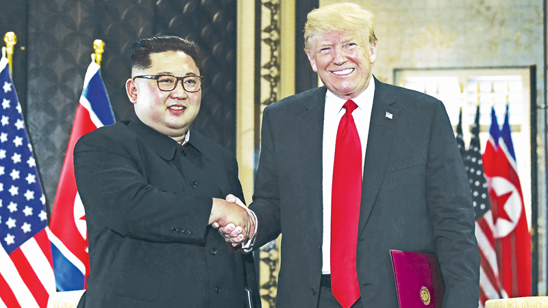 US President Donald Trump (R) and North Korean leader Kim Jong Un shake hands following a signing ceremony during their historic US-North Korea summit, at the Capella Hotel on Sentosa island in Singapore yesterday. - AFP