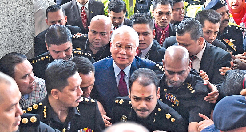 Former Malaysian Prime Minister Najib Razak (C) arrives for a court appearance at the Duta court complex in Kuala Lumpur yesterday. - AFP