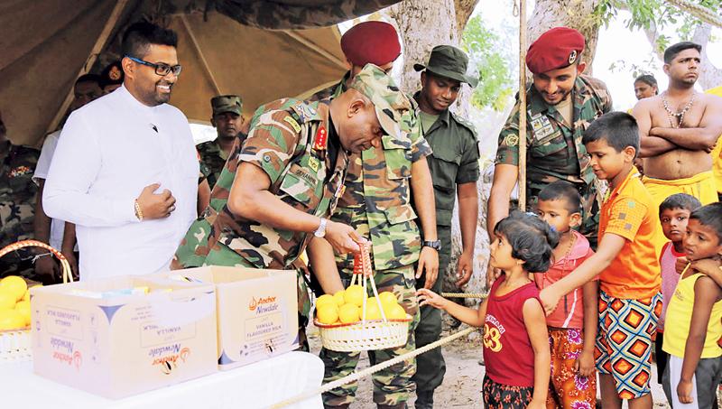 Army Commander Lt. Gen. Mahesh Senanayake distributes food items to the pilgrims.