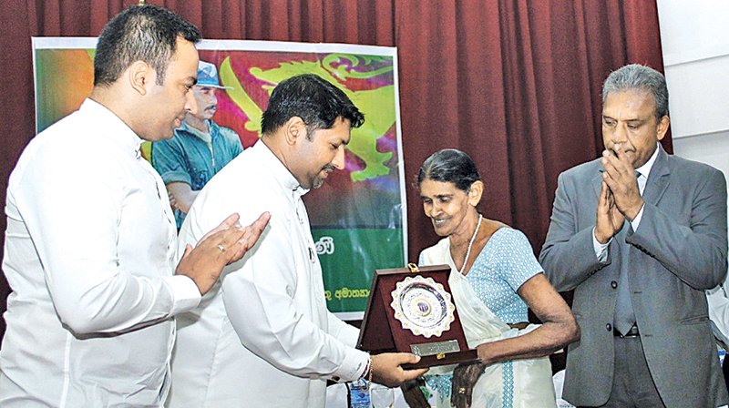State Defence Minister Ruwan Wijewardene presenting a memento to the mother of war hero Corporal Gamini Kularathne, while MP Harshana Rajakaruna and Defence Secretary Kapila Waidyaratne PC look on. Picture by Roshan Pitipana.
