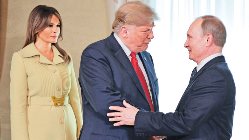 US President Donald Trump (C) shakes hands with Russia's President Vladimir Putin next to US First Lady Melania Trump ahead of a meeting in Helsinki yesterday. - AFP