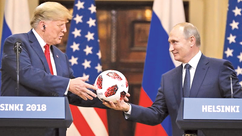Russian President Vladimir Putin gives a soccer ball to U.S. President Donald Trump during a press conference after their Summit at the Presidential Palace in Helsinki, Finland on Monday.