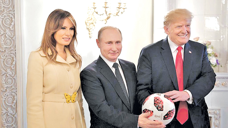 US President Donald Trump and First Lady Melania Trump flank Vladimir Putin as the Russian president gifted a football in Helsinki, Finland.