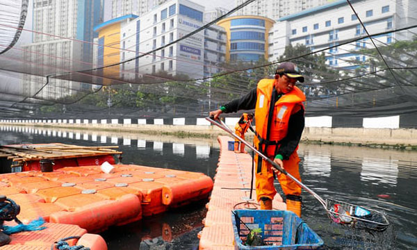 """A worker collects rubbish from a section of the covered river. Aerators and """"nano bubble"""" technology are also being used to help break down organic material."""