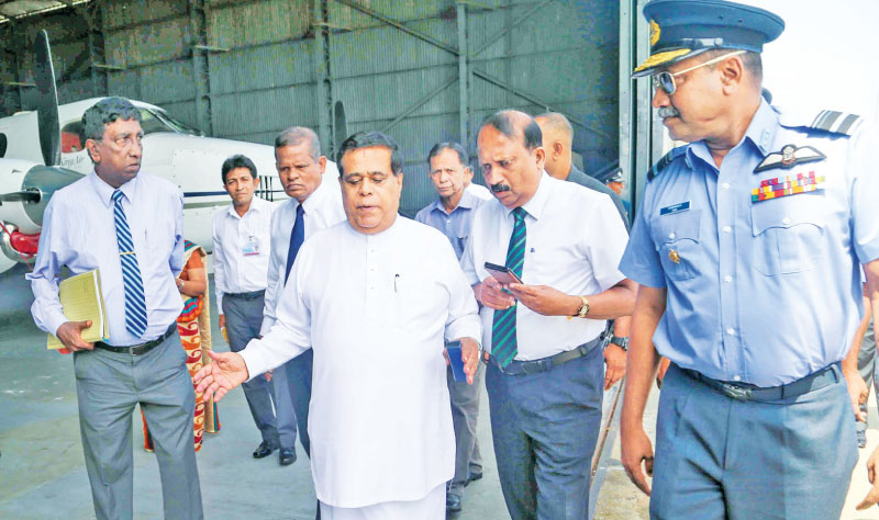 Transport and Civil Aviation Minister Nimal Siripala de Silva and aviation and Air Force officials at the Ratmalana Airport yesterday. Picture by Roshan Pitipana