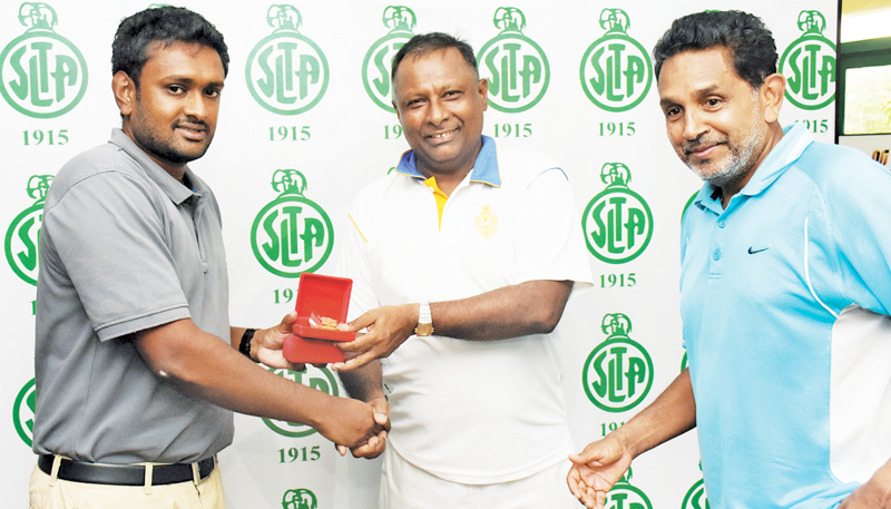 Over 55 doubles winners Sri Lanka's Suresh Subramaniam and Dan Mukunthan receiv the medals from ITF Supervisor Dinusha Wijesuriya