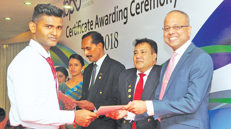 Minister Sagala Rathnayake handing over a certificate to a youth who had completed his training programme. Pic by Wasitha Patabendige