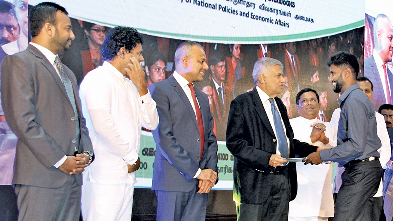 Prime Minister Ranil Wickremesinghe handing over letters of appointment to graduates recruited as development officers to the government service. Around 4,100 graduates received their letters of appointment during the ceremony at Temple Trees yesterday. Ministers Sagala Ratnayaka, Vajira Abeywardena, State Minister Niroshan Perera, MPs Hesha Vithana and  Kavinda Jayawardena were also present. Picture by Hirantha Gunetilake