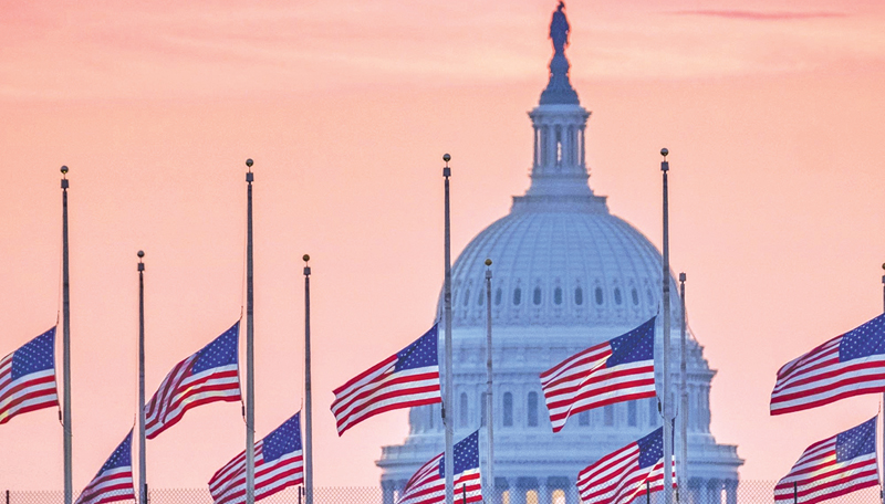 Flags flying at half-staff in honour of Sen. John McCain frame the U.S. Capitol at daybreak in Washington.