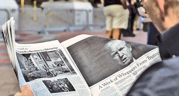 A man reads an article by The New York Times on Donald Trump.
