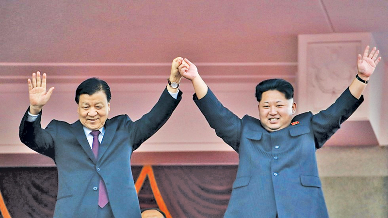 North Korean leader Kim Jong Un and senior Chinsese Communist Party official Liu Yunshan raise hands together and wave to the audience from the balcony, during the 70th anniversary of the founding of the ruling Workers' Party of Korea in Pyongyang. - AFP