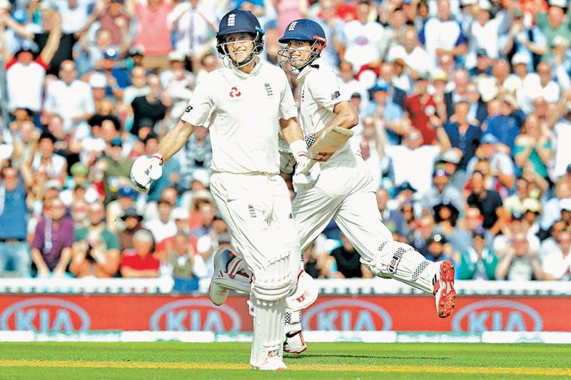 England's Joe Root (L) reacts as England's Alastair Cook smiles after reacing his century during play on the fourth day of the fifth Test cricket match between England and India at The Oval in London on September 10. AFP