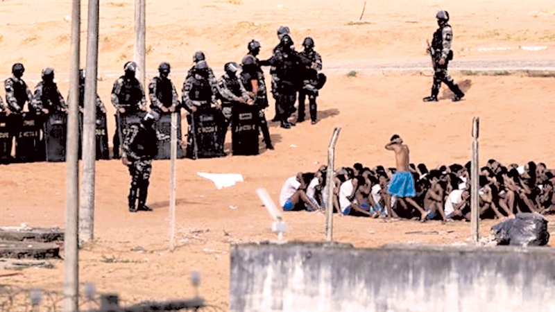 Brazilian military police stand near some of the prisoners recaptured after the prison break.