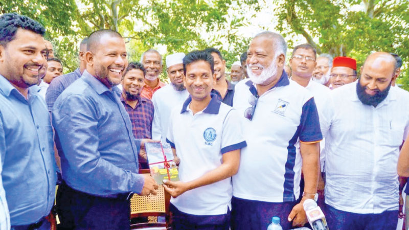 Industry and Commerce Minister Rishad Bathiudeen receives a copy of the book from author M.L.Sarifdeen at the event.