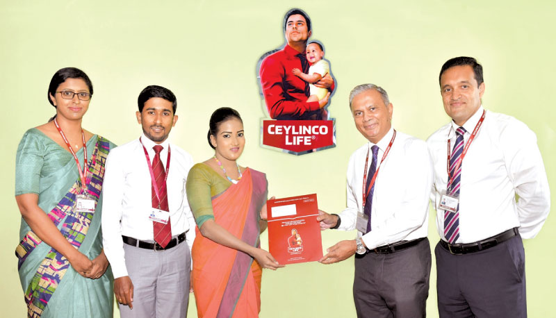 Ceylinco Life Deputy CEO Thushara Ranasinghe presents a 'Guru Abhiman'  policy to the first customer H.G.S. Hettigoda in the presence of the  company's Senior Deputy General Manager  Marketing  Samitha Hemachandra, Category Manager  Marketing  P. H. Samarasinghe  and  Agency Supervisor Akuressa Branch G.M. Ahangama.
