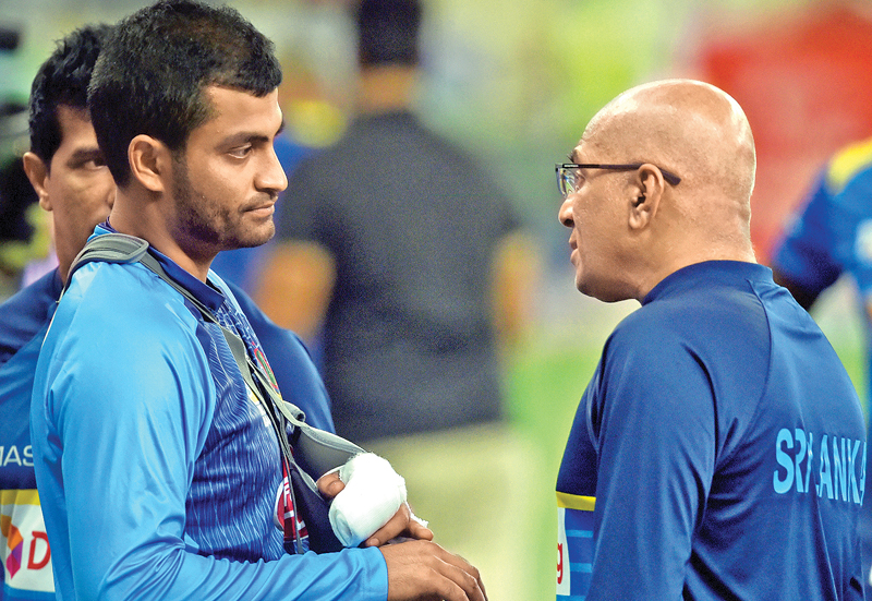 Sri Lanka coach Chandika Hathurusingha has a word with Pakistan opener Tamim Iqbal who has been ruled out of the Asia Cup with a fractured left wrist sustained during the match against Sri Lanka at Dubai on Saturday. AFP