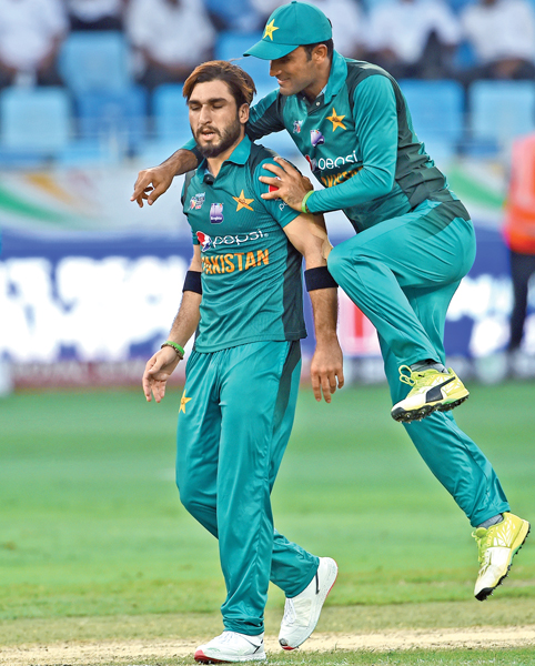 Pakistan fast bowler Usman Khan (L) celebrates with teammate after he dismissed Hong Kong batsman Scott McKechnie during the Asia Cup cricket match played at the Dubai International Cricket Stadium in Dubai on Sunday.  AFP