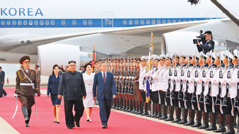 North Korean leader Kim Jong Un (front L) and South Korean President Moon Jae-in (front R) review honour guards during a welcoming ceremony at Pyongyang airport  yesterday. - AFP