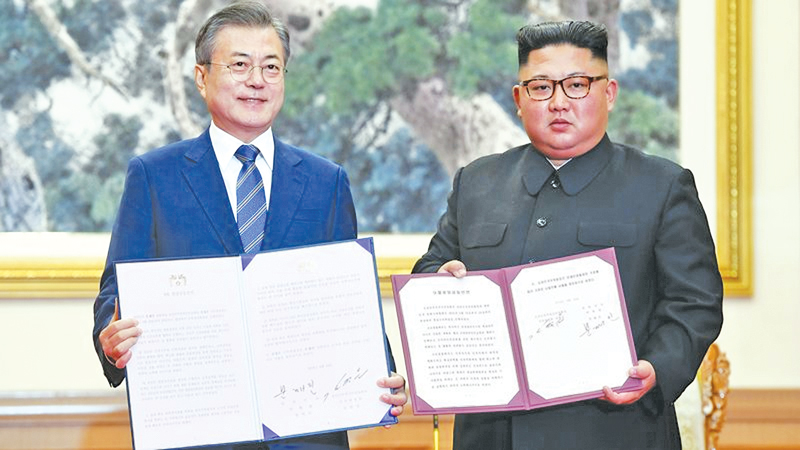 South Korean President Moon Jae-in and North Korean leader Kim Jong Un exchange documents at a joint signing ceremony  after their summit in Pyongyang.- AFP